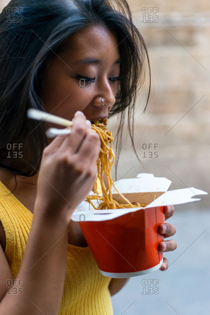 Young Asiatic woman eating a chinese take-away on the street in Barcelona, Spain