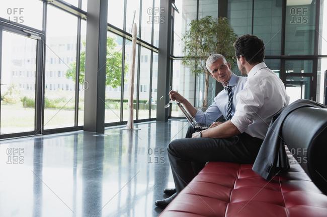 Germany- Businessmen talking in lobby