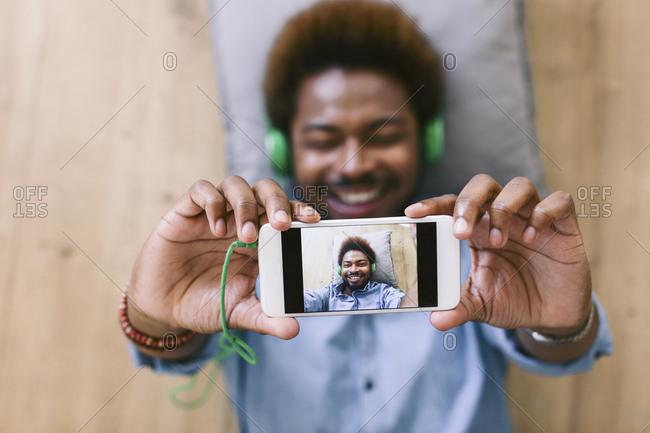 Young Afro American man lying on floor- taking selfie