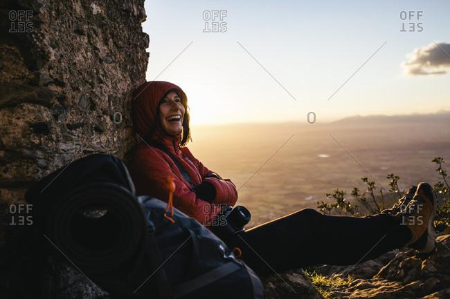 Spain- Catalunya- Girona- happy female hiker resting at stone structure