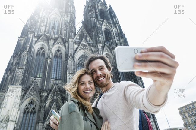 Germany- Cologne- portrait of young couple taking a selfie in front of Cologne Cathedral