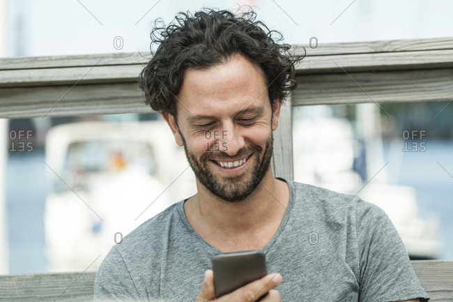 Smiling man outdoors looking on cell phone