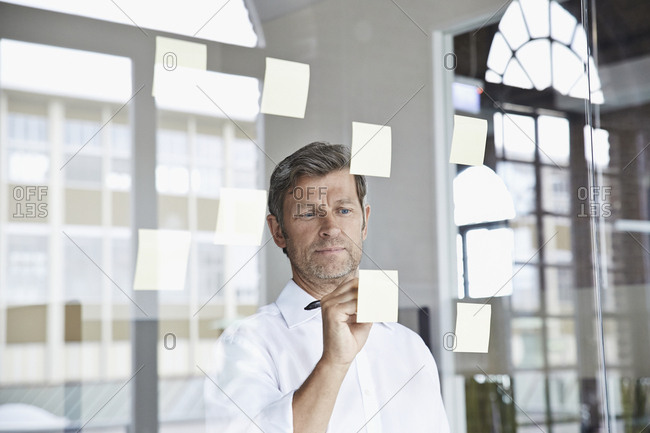 Businessman writing on sticky note on glass pane in office