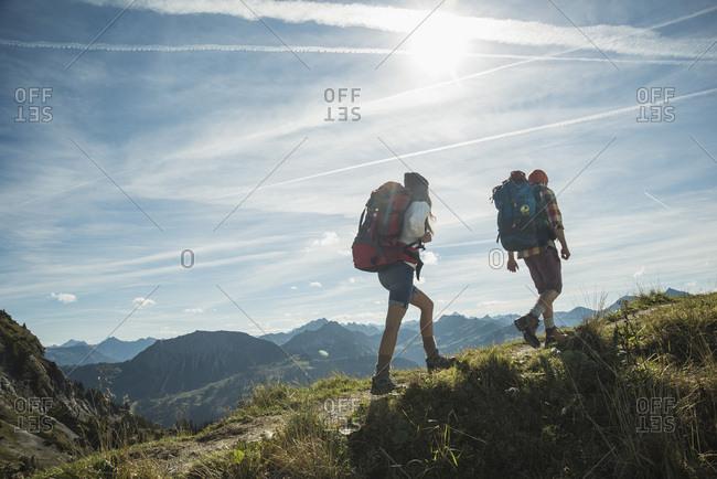 Austria- Tyrol- Tannheimer Tal- young couple hiking on mountain trail