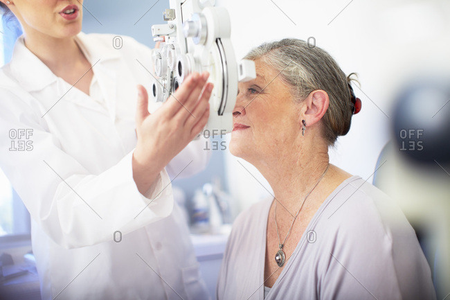 Eye doctor examining senior woman's vision