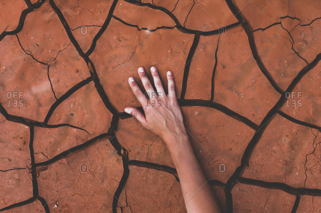 A hand touching cracked earth