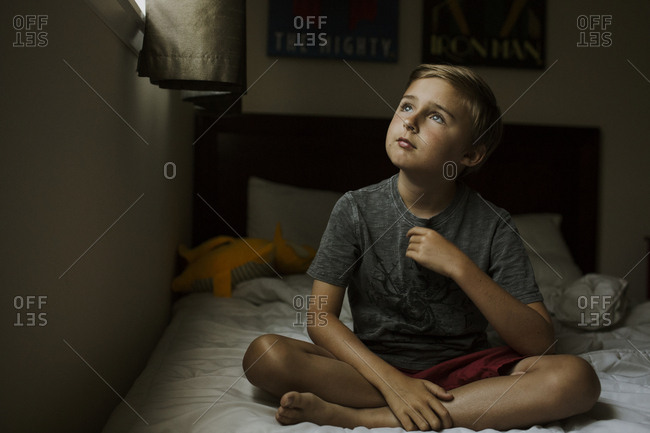 Boy looking up sitting on bed