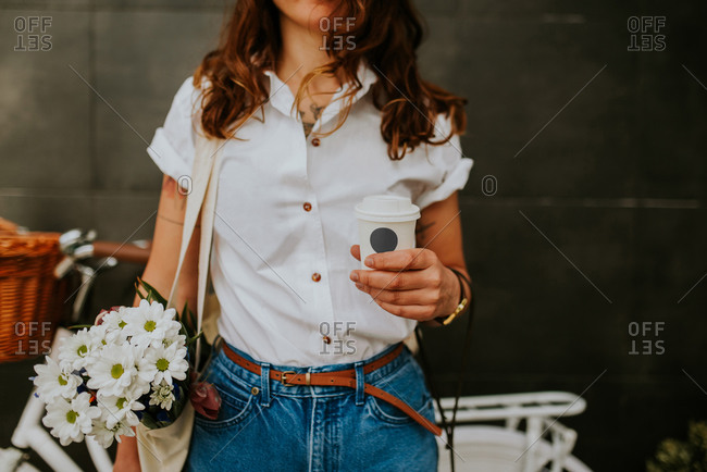 Hip woman with coffee and flowers