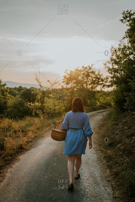 Woman walking path with basket