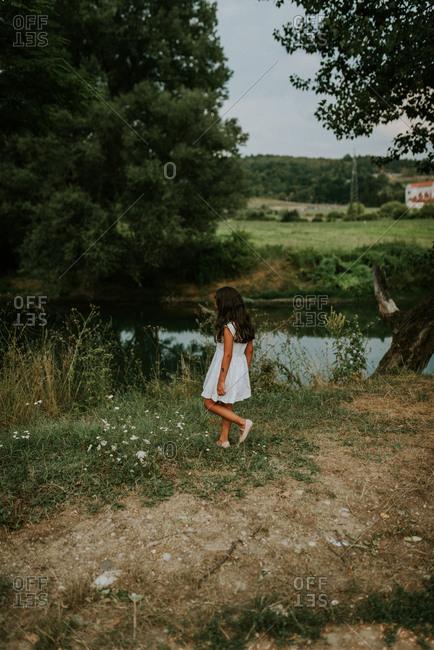 Girl wandering by farmland lake