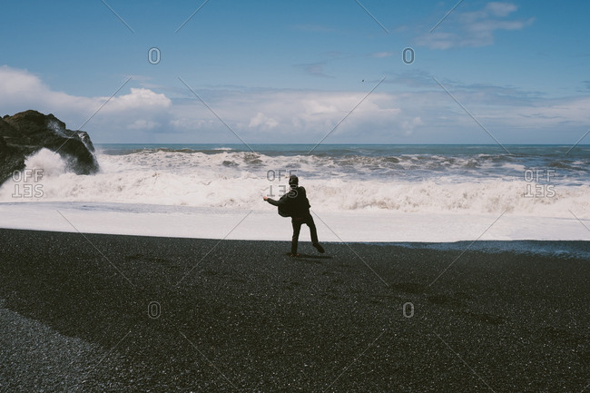 Man throwing rocks into the ocean