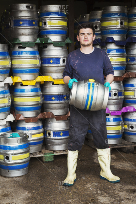 Man working in a brewery, standing next to a stack of metal beer kegs, holding beer keg
