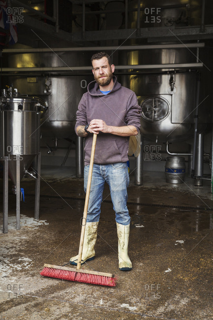 Man working in a brewery, cleaning floor with a large broom