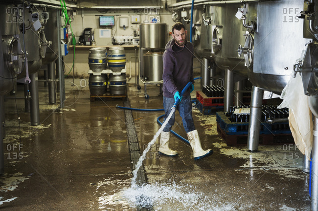 Man working in a brewery, cleaning floor with water hose