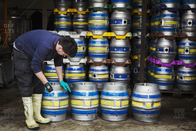 Man working in a brewery, standing next to a stack of metal beer kegs, holding mallet