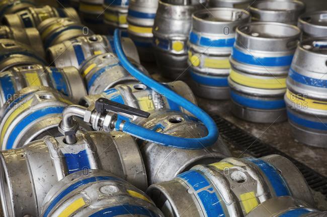 Close up of metal beer kegs being filled in a brewery