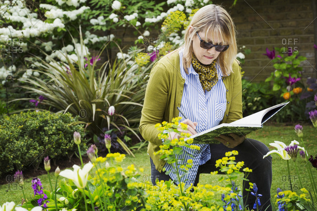 Woman wearing sunglasses standing in a garden by a flowerbed, drawing in a sketchbook