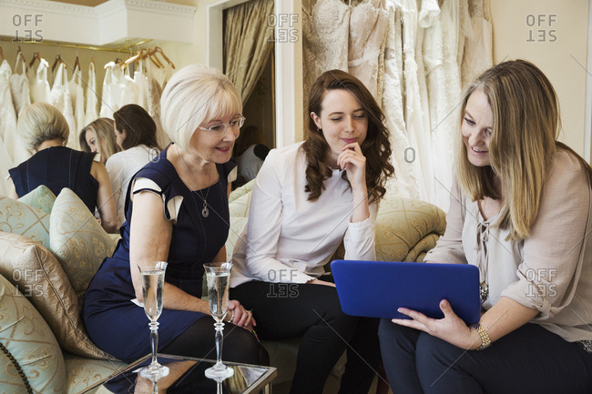 Three women in a wedding dress shop, one bride to be and two retail advisors looking at a digital tablet.  Two glasses of champagne on the table