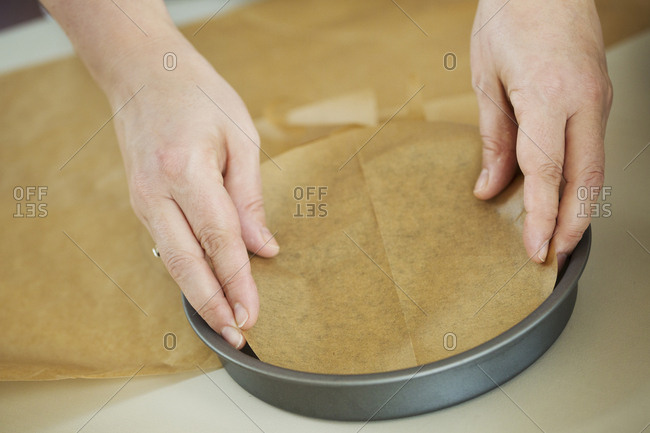 Close up high angle view of person lining the bottom of a round baking tin with baking paper