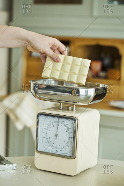 Close up of hand placing a bar of white chocolate onto an analogue kitchen scale