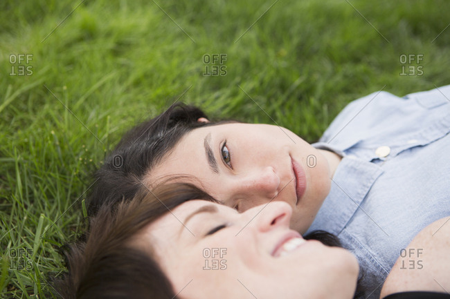 A same sex couple, two women lying on the grass, looking tenderly at each other, relaxing