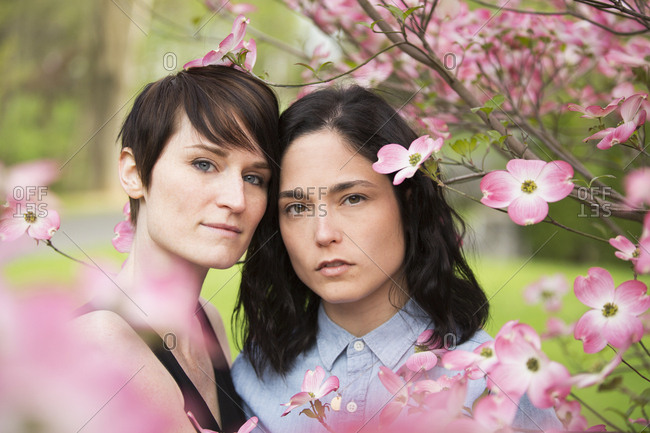 A same sex couple, two women under the branches of a flowering tree