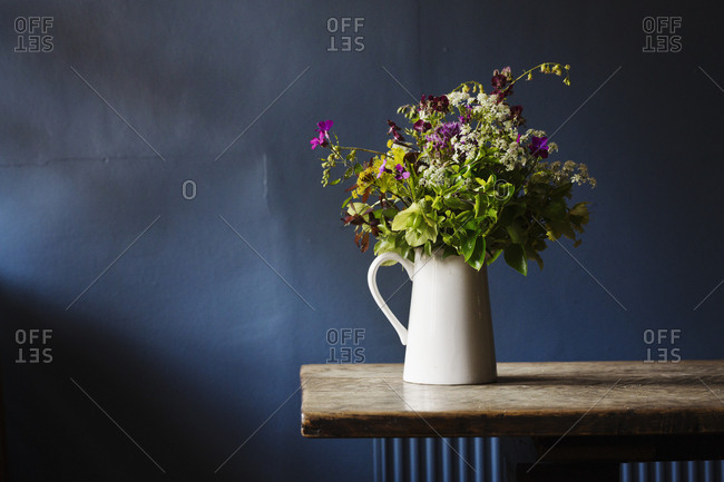 Close up of white jug with bunch of wild flowers on a wooden table, blue wall behind
