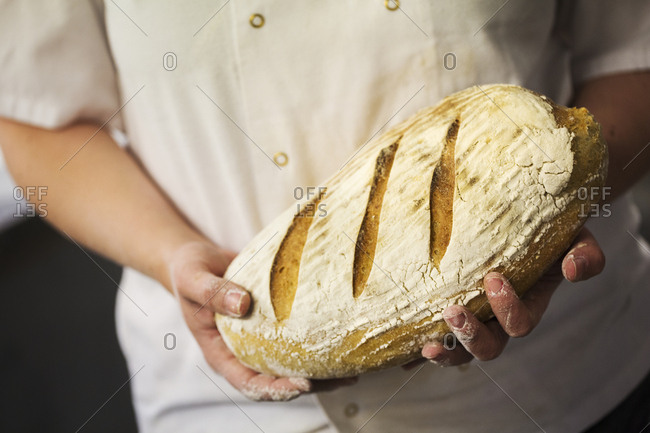 Close up of person holding a freshly baked loaf of bread