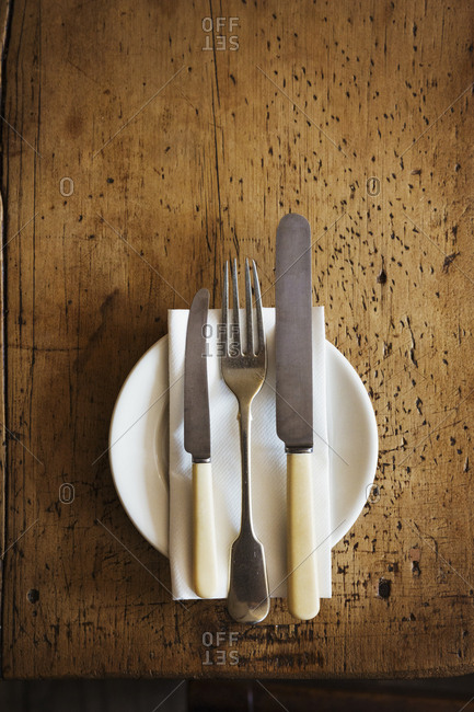 Close up high angle view of plate with knives and fork and a serviette on a rustic wooden table