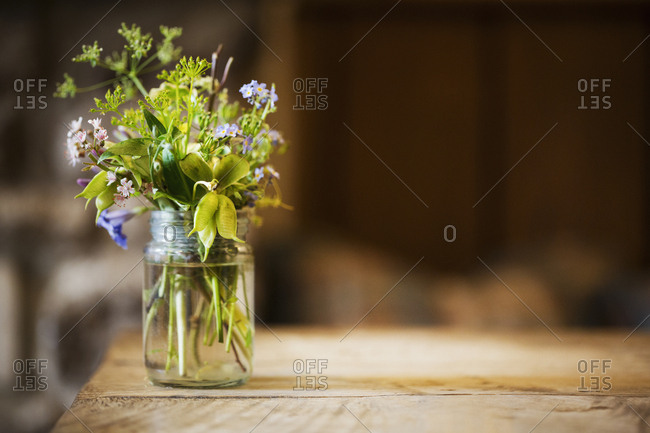 Close up of glass jar with small bunch of wild flowers on a wooden table
