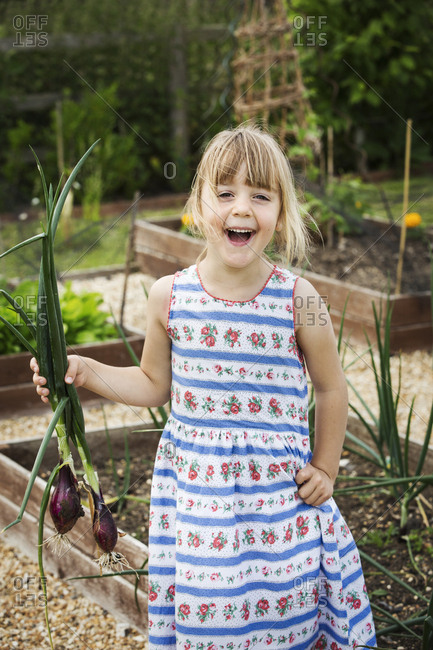 Smiling girl in a sundress standing in a garden, holding a bunch of onions, looking at camera