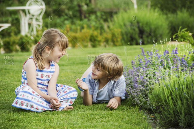 A girl sitting on the grass talking to her brother lying beside her on a lawn in a garden