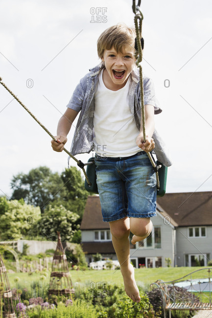 Smiling boy wearing shirt and denim shorts on a swing in a garden