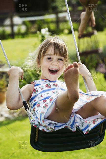 Smiling girl wearing a sundress on a swing in a garden
