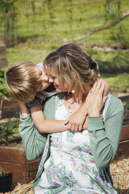 A mother and son, a woman sitting on a garden bench, her son kissing her on the cheek
