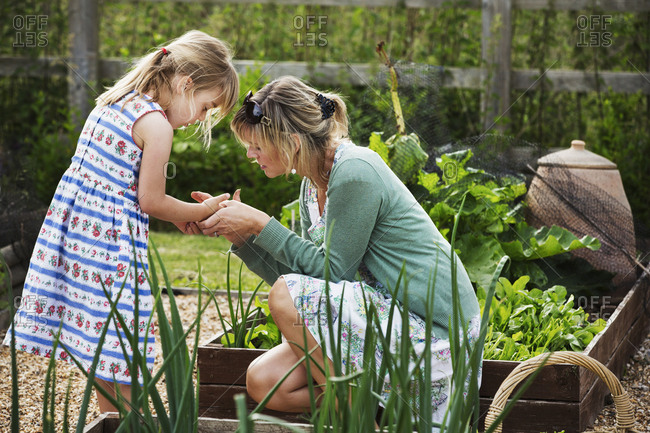 Woman kneeling in a garden by a raised vegetable bed, looking at the hand of a young girl beside her