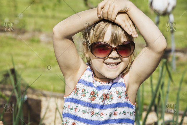 Girl in a sundress wearing sunglasses, hands on head, smiling at camera