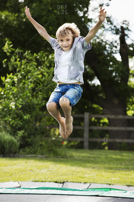 Boy wearing shirt and denim shorts jumping on a trampoline in a garden