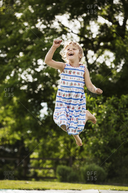 Girl in a sundress jumping on a trampoline in a garden