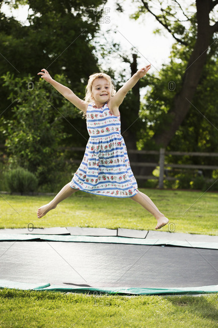 Girl in a sundress jumping on a trampoline set in the ground, in a garden