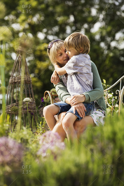 Woman sitting in a garden with a boy on her lap, hugging