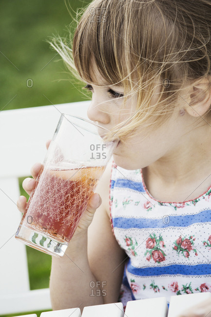 Girl sitting outdoors on a bench, sipping from a drinking glass