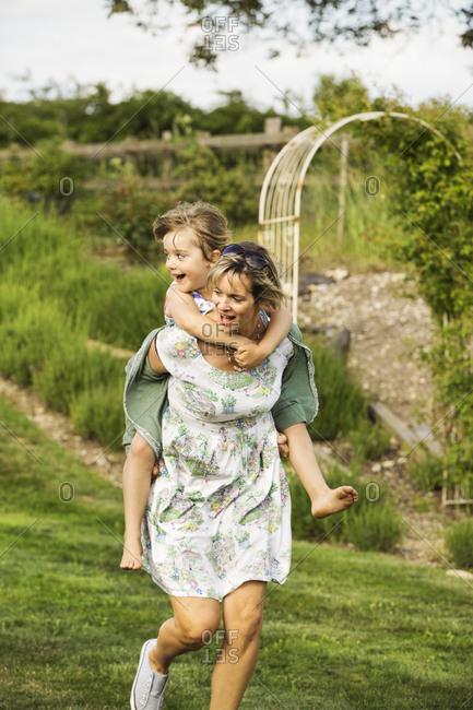 Woman in a sundress running across a lawn, giving a child a piggyback