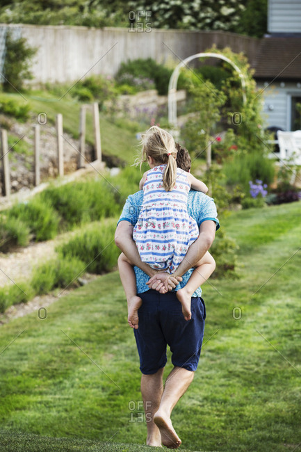 Rear view of a man walking across a lawn, carrying a girl on his back