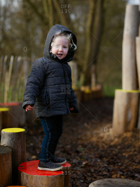A smiling sporty casual young girl playing and having fun in public park on a wooden path made of painted tree trunks surrounded by trees in autumn
