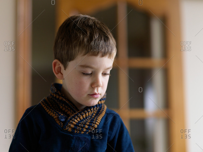 A portrait of a young boy thinking at home with a short depth of field and blurred background