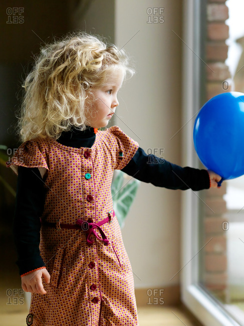 A portrait of a smiling young blonde girl looking through the window holding a blue birthday balloon at home with a short depth of field and blurred background