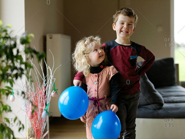 Two kids, brother and sister posing and having fun with blue birthday balloon at home with a short depth of field