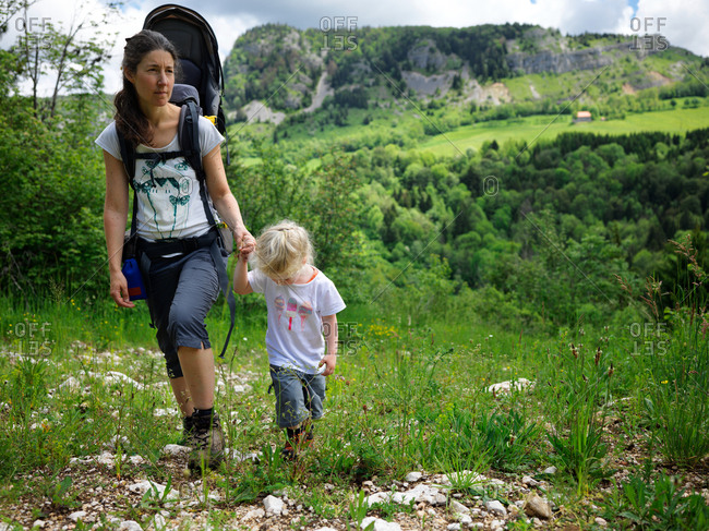 A young girl holds the hand of her mother walking a flowery path during a trail in the French Jura with mountains on the background