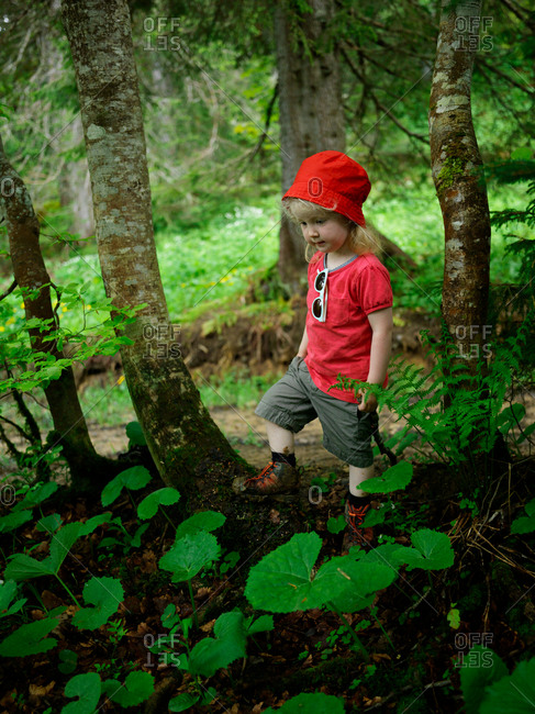 A young girl with a red hat walking alone on a forest path during a trail in the French Jura